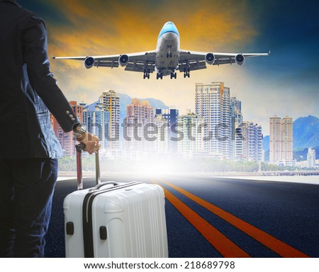 business man and luggage standing on airport runways with passenger jet plane flying above airport runway use for aircraft transport ,traveling ,journey trip with airline  - stock photo
