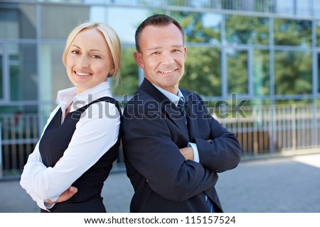Business man and smiling woman leaning back on back outside the office - stock photo