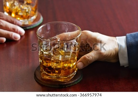 business man and whiskey in hand on wooden table bar background - stock photo