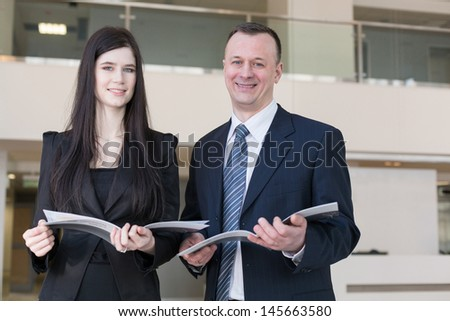Business man and woman are holding magazines