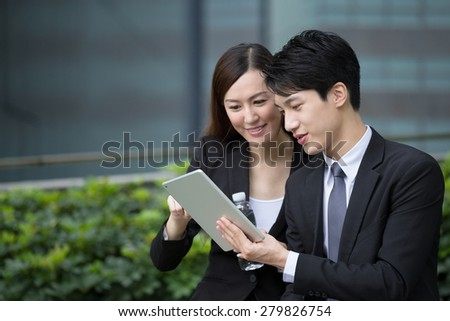 Business man and woman discuss about the financial plan on digital tablet - stock photo