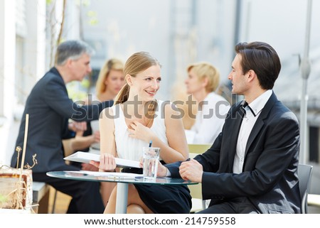 Business man and woman flirting outdoors in a coffee shop - stock photo