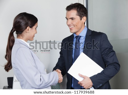 Business man and woman giving handshake in the office - stock photo