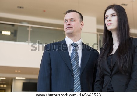 Business man and woman looking into the distance, focus on a man.