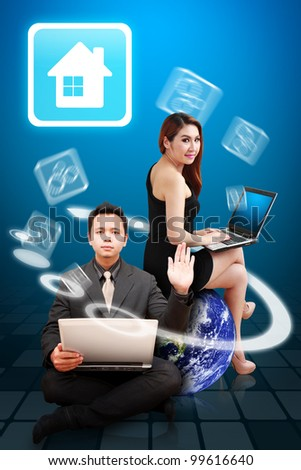 Business man and woman present the house icon from the world : Elements of this image furnished by NASA