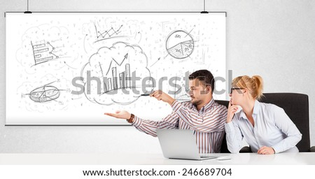 Business man and woman sitting at white table with hand drawn graph charts - stock photo