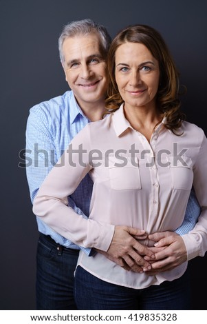Business man and woman stand one behind the other as he holds her about the waist and smiles against a dark blue background - stock photo