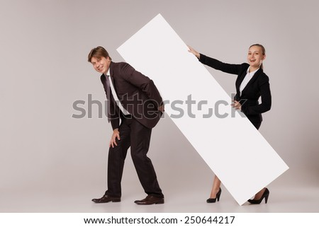 Business man and woman standing on both sides of blank banner the man holding it on his back.  isolated on grey background. Teamwork concept