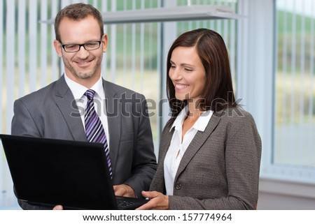 Business man and woman standing side by side in an impromptu meeting using a handheld laptop computer to discuss data - stock photo