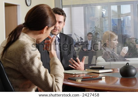 Business man and woman talking in the office - other people in the background - stock photo