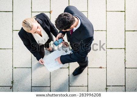 Business man and woman  with newspaper and smart phone standing on square, seen in top view - stock photo