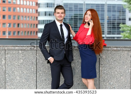 Business man and woman with phone in front of office building in the city