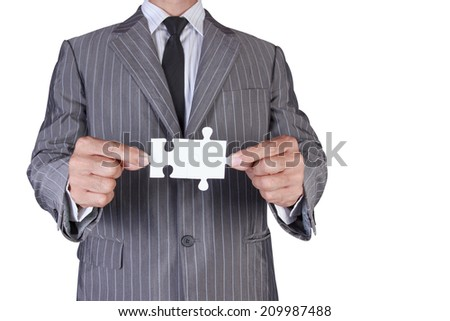 business man assembling jigsaw puzzle isolated on white background with clipping path - stock photo