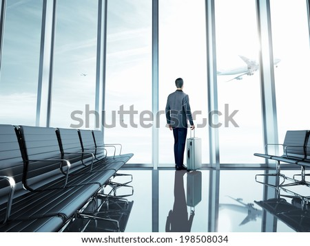 Business man at airport with suitcase - stock photo
