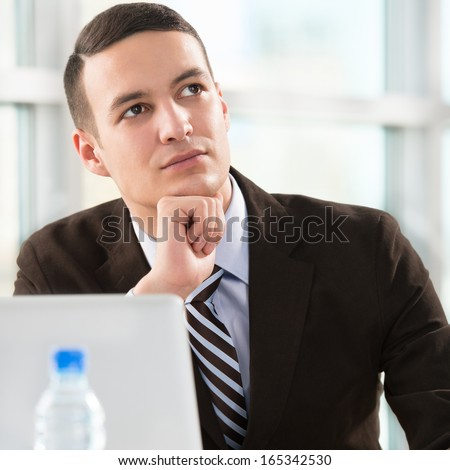 Business man at his office working with laptop and thinking about his future plans - stock photo
