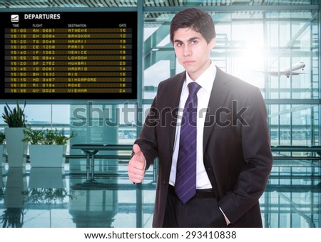 Business man at the airport terminal in front of the departure board - stock photo