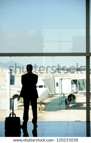Business man at the airport, waiting for his airliner - stock photo
