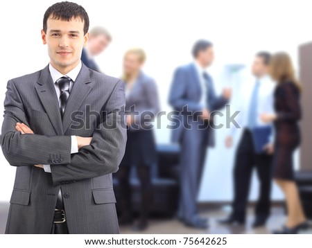 Business man at the office with a group behind him