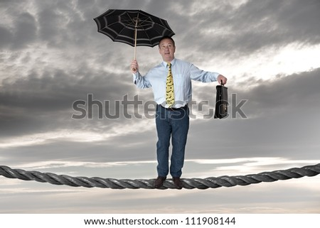 Business man balancing on the rope - stock photo