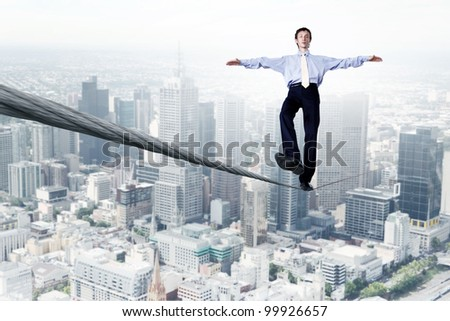 Business man balancing on the rope high in the sky