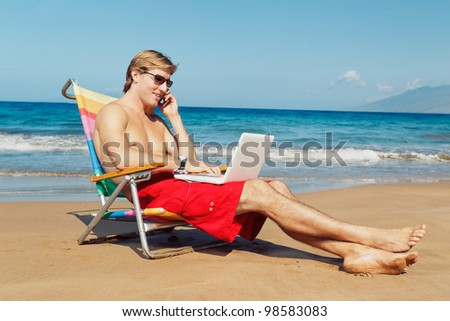 Business man calling by cell phone and working on computer at the beach in Hawaii