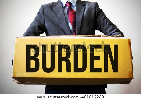 "Business man carrying an old box saying ""BURDEN"" - indicates debt and business burden - stock photo"