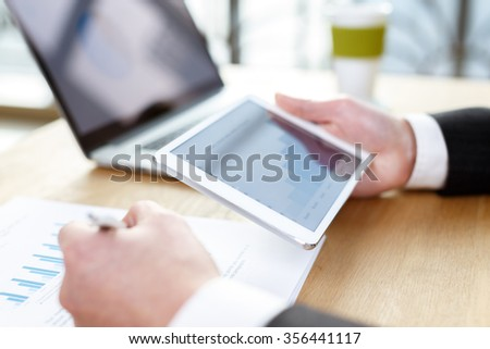 business man checking financial reports on table using computer,digital tablet and mobile phone