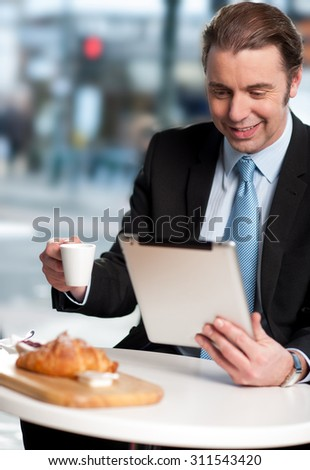 Business man checking mails on his tablet device - stock photo