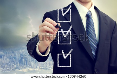 Business man checking off check boxes with cityscape background - stock photo