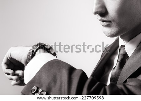 Business man checking time on his wrist watch - stock photo