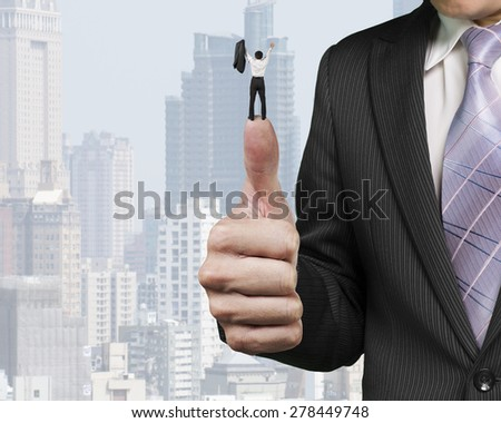 Business man cheering on top of another big thumb with city buildings background - stock photo