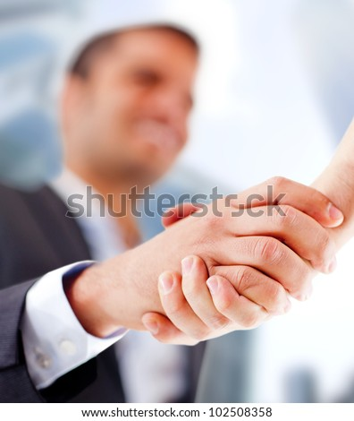 Business man closing a deal with a handshake - stock photo