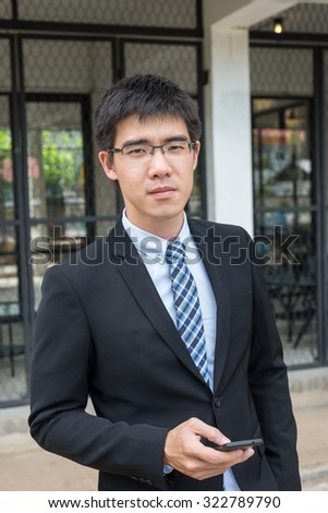 business man concept photo, young and handsome asian business man wearing glasses holding a phone in his hand looking forward  (selective focus technique applied) - stock photo