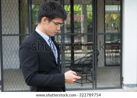 business man concept photo, young and handsome asian business man wearing glasses looking at the phone looking forward on a vintage style coffee shop background  (selective focus technique applied) - stock photo