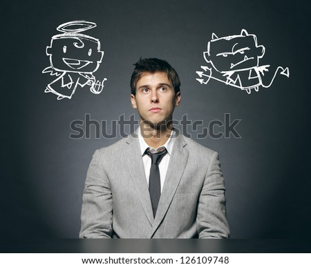 Business man confused with his good and bad conscience - stock photo