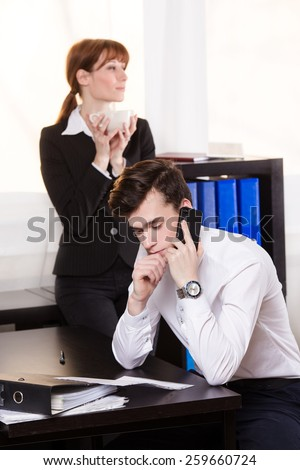 Business man consult someone on the phone and business woman drinking coffee and relax in the office.