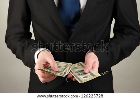 Business man counts money on grey background