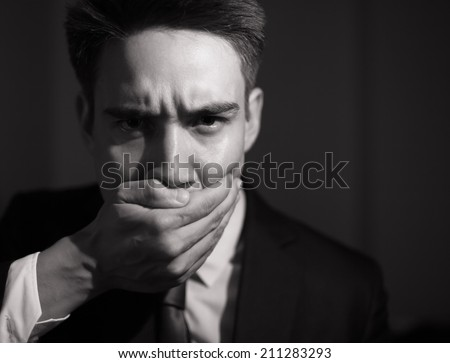 Business man covering his mouth - speak no evil concept.