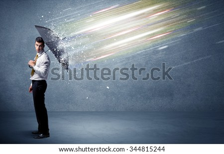 Business man defending light beams with umbrella concept on background - stock photo