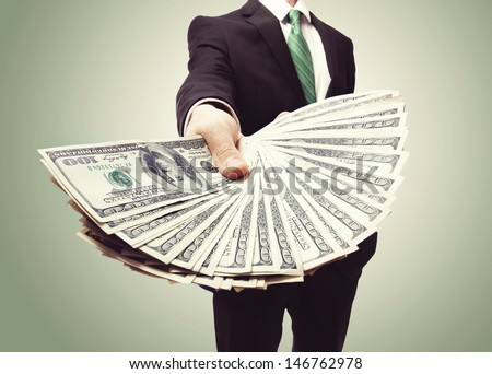 Business Man Displaying a Spread of Cash over a green vintage background - stock photo