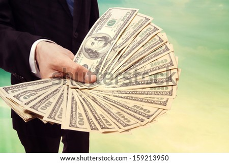 Business Man Displaying a Spread of Cash over Vintage Sky Background - stock photo