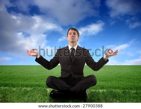 business man doing yoga in a grass field