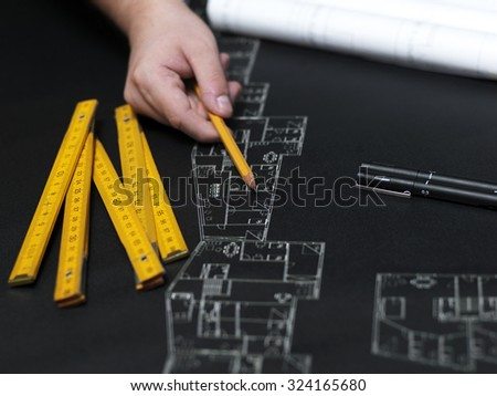 Business man draw buildings and present his architectural project - stock photo
