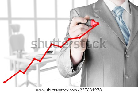 Business man drawing a growing graph - stock photo