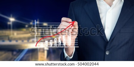Business man drawing a growing graph
