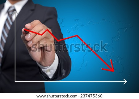 Business man drawing decline graph over blue background - stock photo