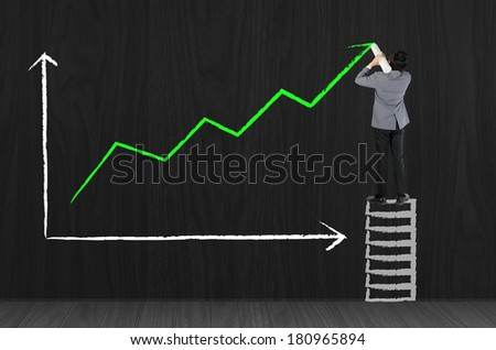 Business man drawing growing green graph - stock photo