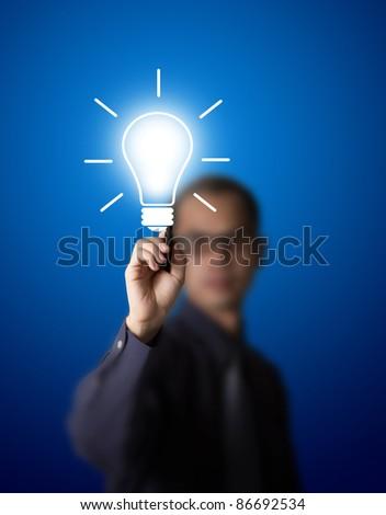 business man drawing light bulb - stock photo