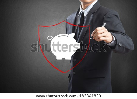 Business man drawing shield protecting piggy bank and money, insurance concept - stock photo