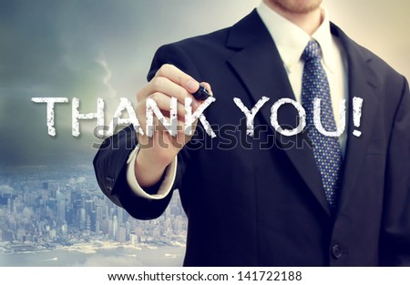 Business man drawing THANK YOU on a big city background - stock photo